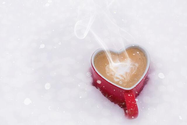 雪の中にハート型のマグカップが置いてある写真