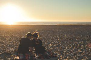 浜辺に座るカップルの写真