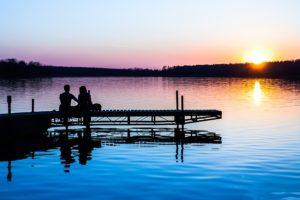 夕日が綺麗な所に座るカップル