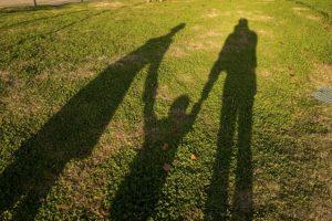 手をつないでいる夫婦と子供の写真