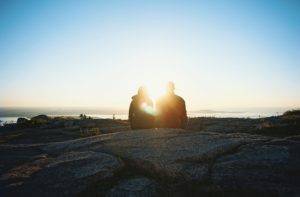 カップルの背景に夕日が綺麗に差している写真